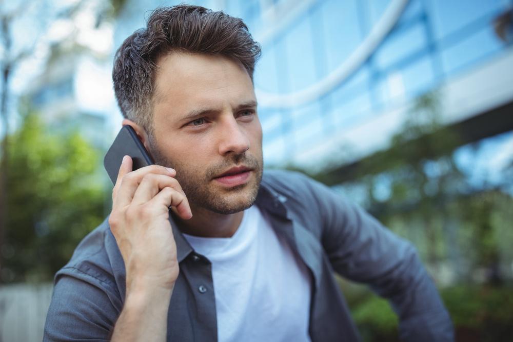 Close-up of handsome man talking on mobile phone