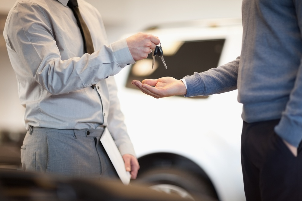 Man giving keys to another man in a car shop