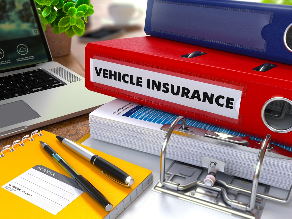 Red Ring Binder with Inscription Vehicle Insurance on Background of Working Table with Office Supplies, Laptop, Reports. Toned Illustration. Business Concept on Blurred Background.